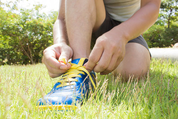 Man Tying Shoes On Green Grass