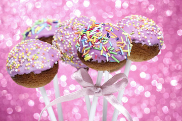 Pink cake pops decorated with colorful sprinkles