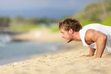 Push-ups - man fitness model training on beach