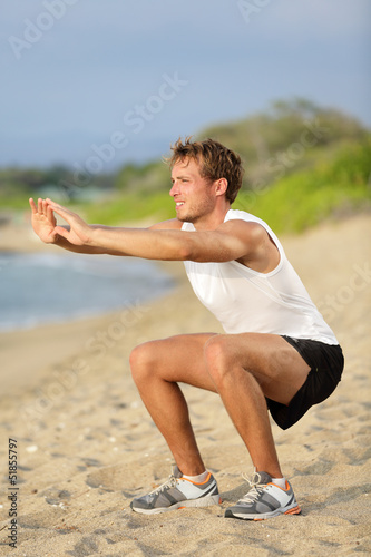 Fitness man training air squat exercise on beach