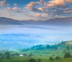 Summer landscape with a mountain village in the mist