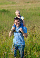 father and child on wild summer field