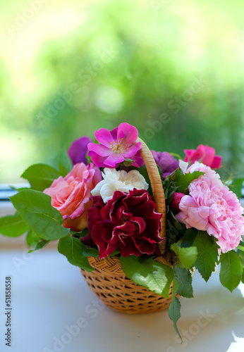 colorful roses in basket on window-sill