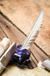 Blue ink with feather on old wooden table
