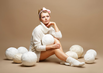 Embroidery. Woman in White Knitwear with Heap Balls of Yarn