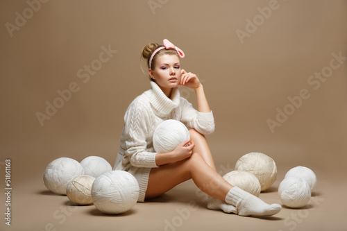 Housework. Woman in White Tricot with Woolen Balls. Seamstress