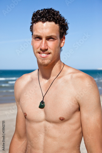 Handsome fit young man on the beach. Portrait
