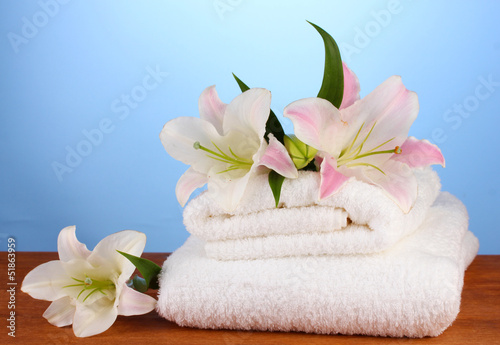 stack of towels with pink lily on blue background