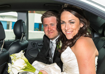 Bride and Groom sitting in the wedding Car