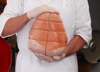 Carnicero sujetando una porción de jamón cocido Italiano.