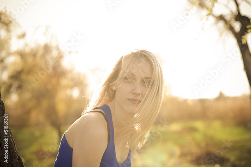 Beautiful blonde girl model looks away in the sun rays