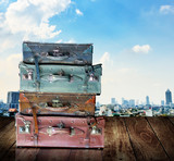Vintage travel luggage on wooden wall with city view background poster
