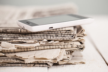 Pile of newspapers with smartphone on it