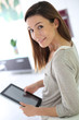 Young cheerful woman using digital tablet