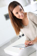 Young cheerful woman using electronic tablet