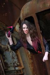 Wütende junge Frau mit Schuh im Fenster eines alten Baggers.