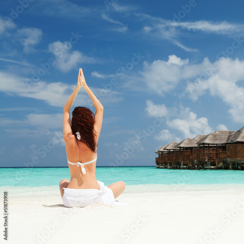 woman doing yoga exercises on the beach
