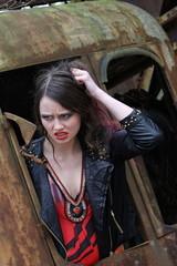 Wütende junge Frau  im Fenster eines alten Baggers..