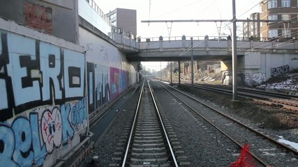 View of rails from the back of a train going through a city