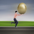 Businessman run with gold egg on track field