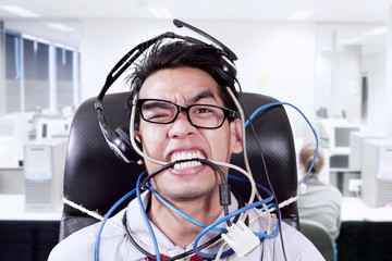 Stress businessman biting cables at office