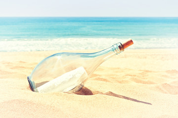 A bottle with a letter of distress in the sand on the beach. In