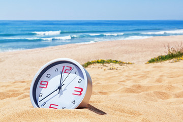 Classic analog clocks in the sand on the beach near the sea. For