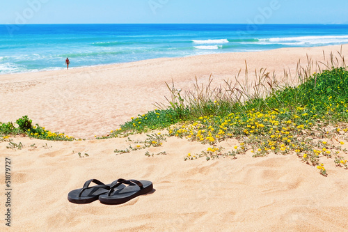 Flip-flops on the background of the beautiful beach and the sea.
