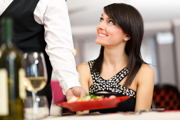 Waiter serving a woman in a restaurant