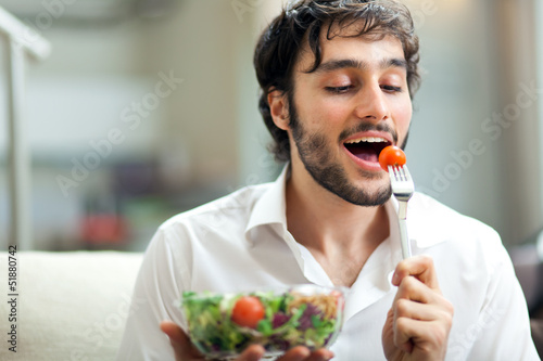 Man eating a salad on the sofa
