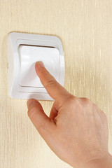 Hand turn off the light switch on the wall