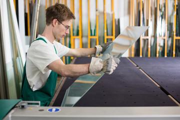 Glazier handling piece of glass in workshop