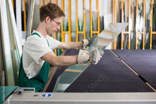 Glazier handling piece of glass in workshop - 51884997