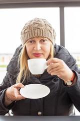 Señora disfrutando de una taza del cafe.