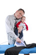 man is ironing, and holding baby