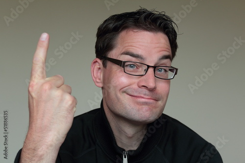Attractive caucasian man with glasses pointing up
