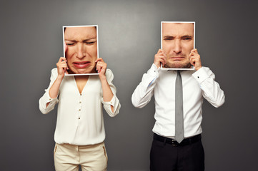 man and woman holding frames with sad faces
