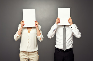 man and woman holding white papers