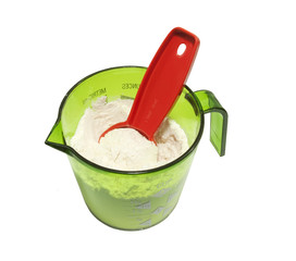 green measuring cup with flour and 15 ml measuring spoon
