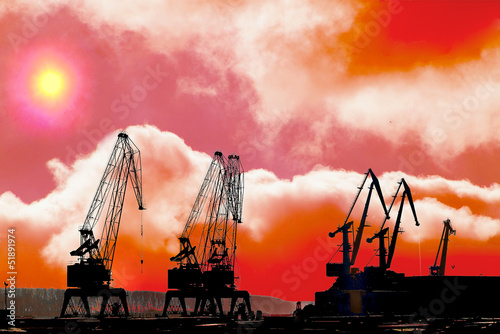 Silhouettes of cranes in the shipyard. at sunset