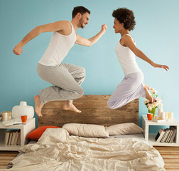 Happy Couple Jumping on Bed