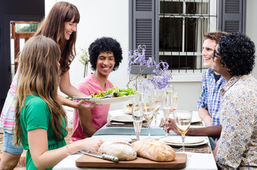 Group of friends smiling and laughing at lunch