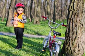Cute little boy with his bike in woodland