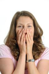 Lachende,junge Frau haelt ihre Heande vor das Gesicht.