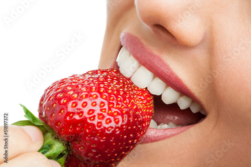 Poster, Tablou Extreme close up of teeth biting strawberry.