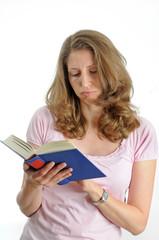 Junge,bruenette Frau haelt ein Buch in der Hand.