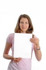 Junge,bruenette Frau haelt ein weisses Plakat hoch.