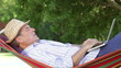 Senior Man In Hammock Using Laptop Computer