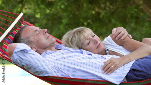 Romantic Senior Couple Relaxing In Garden Hammock Together