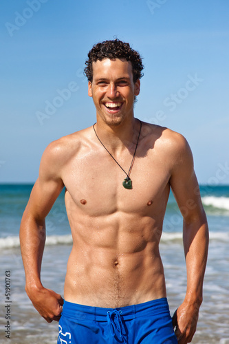 Handsome fit young man laughing on the beach